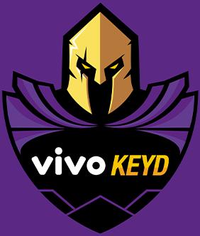 """Logotipo da empresa Vivo Keyd. O logo tem a forma de um escudo, com a parte superior representando um cavaleiro medieval. O nome """"Vivo Keyd"""" está escrito nas cores branca e amarela."""