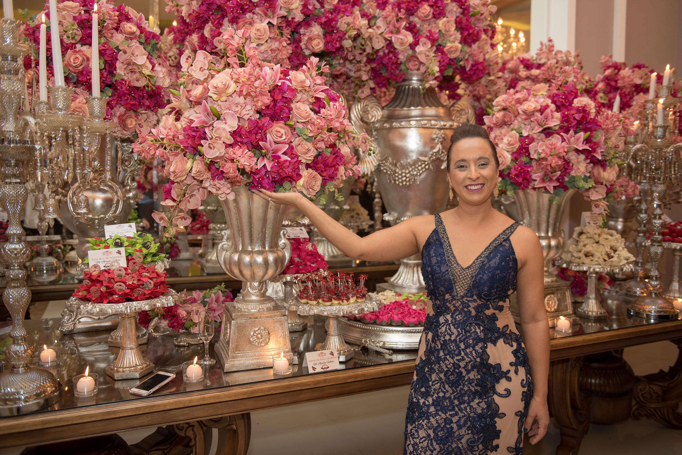 Val du Arte no aniversário de 50 anos da cantora Mara Maravilha em frente aos arranjos florais da mesa de bolo da Mansão Adélia Prado